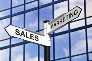Concept image of Sales & Marketing on a signpost against a modern glass office building.
